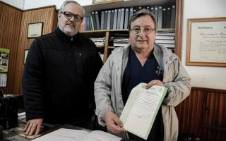 Cumba mostrando el acta compromiso firmada ante escribano